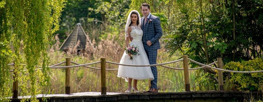 Outdoor view of our wedding venue in south Lincolnshire, with the rustic bridge over the lake
