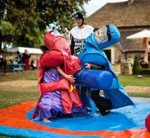 Players in wrestling suits at medieval themed party